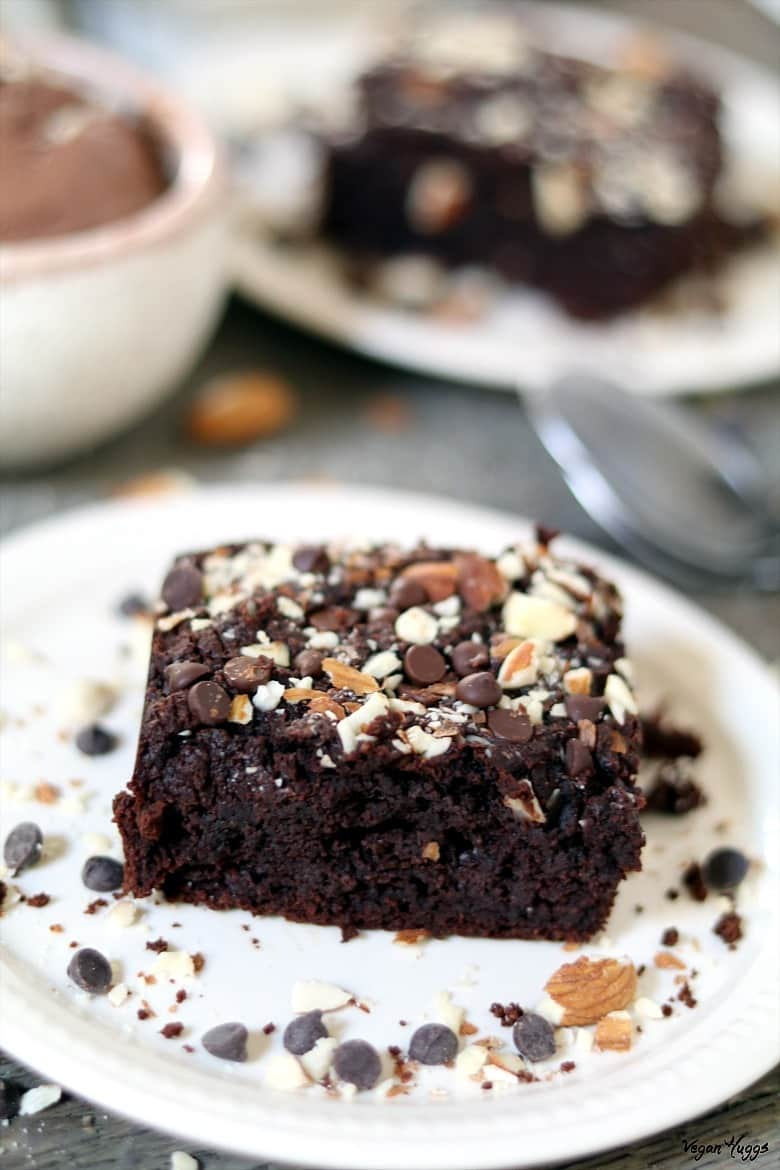 Close up view of a brownie on a white plate. Ice cream and spoon in the background.