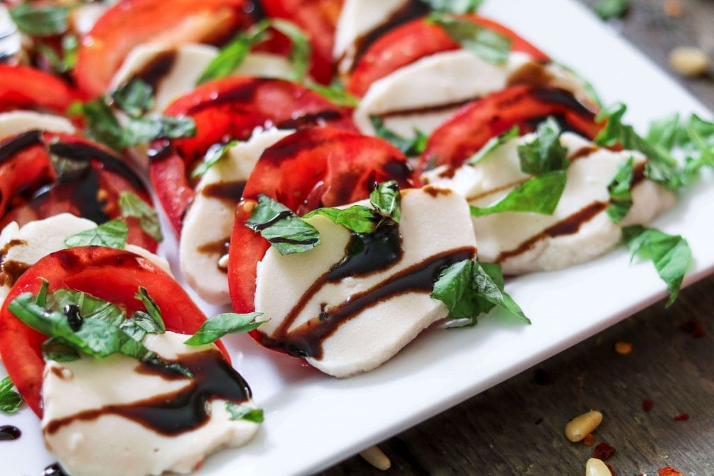 Vegan Mozzarella Cheese sliced on a white serving plate on an angled view. Topped with fresh basil and balsamic glaze.
