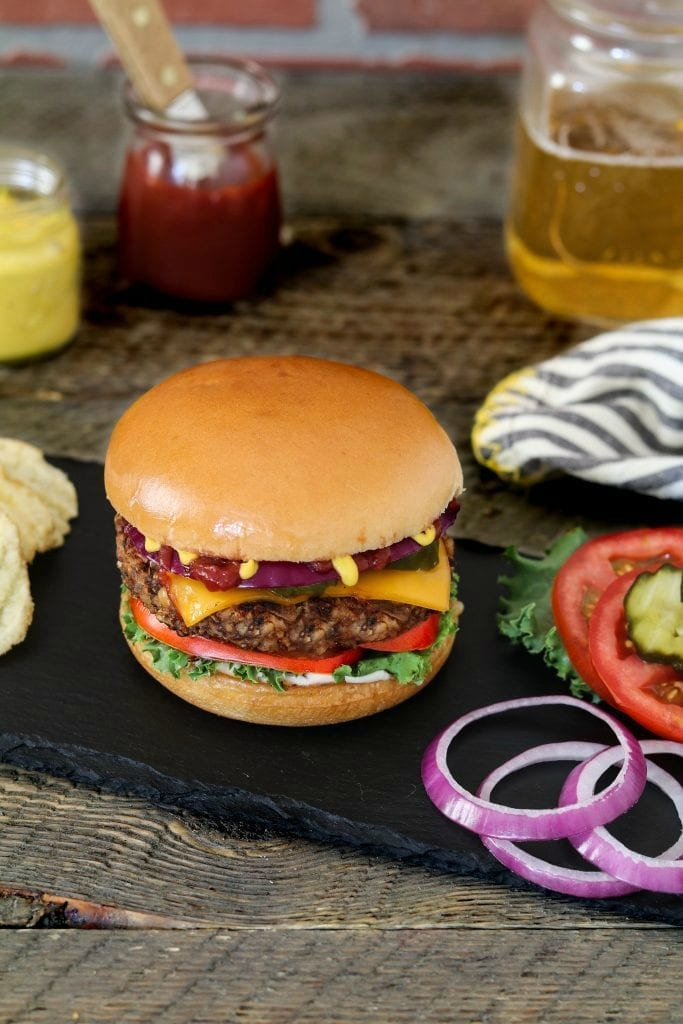 Bean and Mushroom Burger with onion, pickles and tomato on the side.
