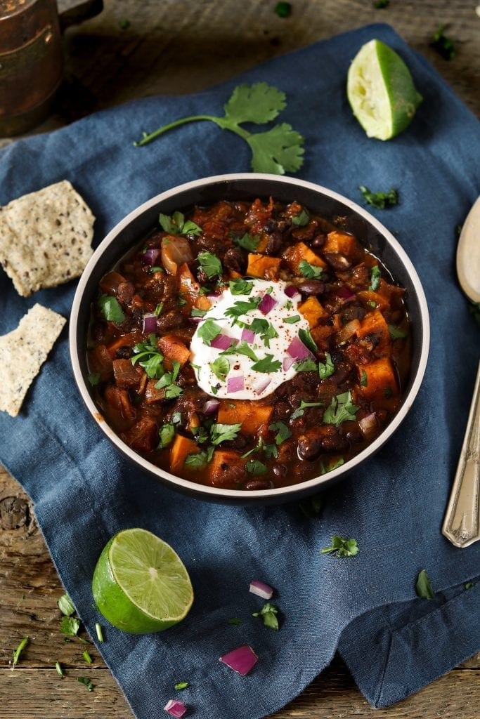 overhead view of sweet potato black bean chili in a black bowl with sour cream on top.
