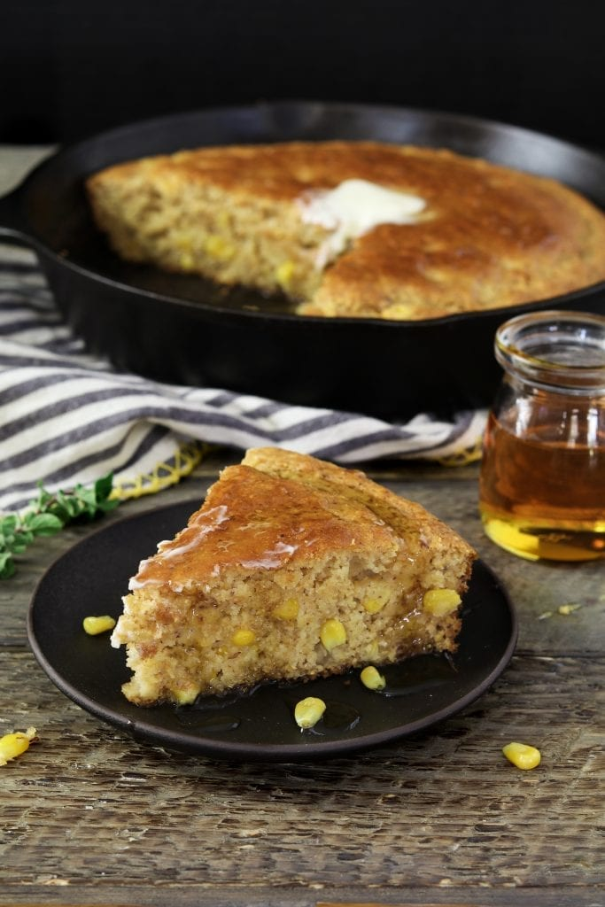 slice of cornbread on a black plate. Skillet on top of striped napkin in the background.