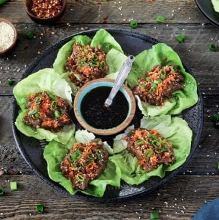 vegan lettuce wraps on a black plate. Topped with green onions, sesame seeds and carrots.