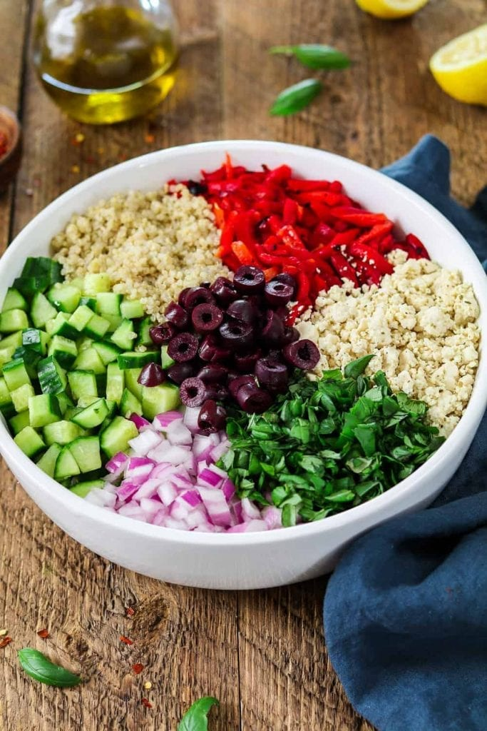 Large white bowl filled with Mediterranean Quinoa Salad. Ingredients are separated.