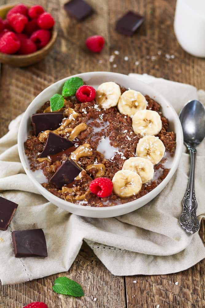 Breakfast quinoa bowl topped with bananas, chocolate and peanut butter. Raspberries in a small bowl on the side.