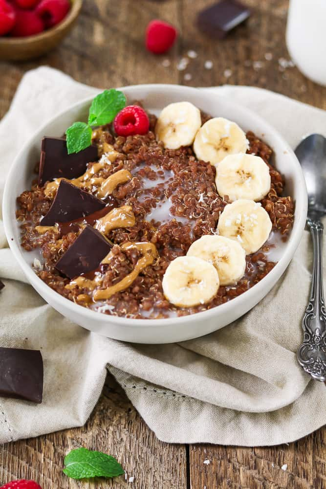 Quinoa Breakfast Bowl topped with banana coins, chocolate chunks and swirled peanut butter.