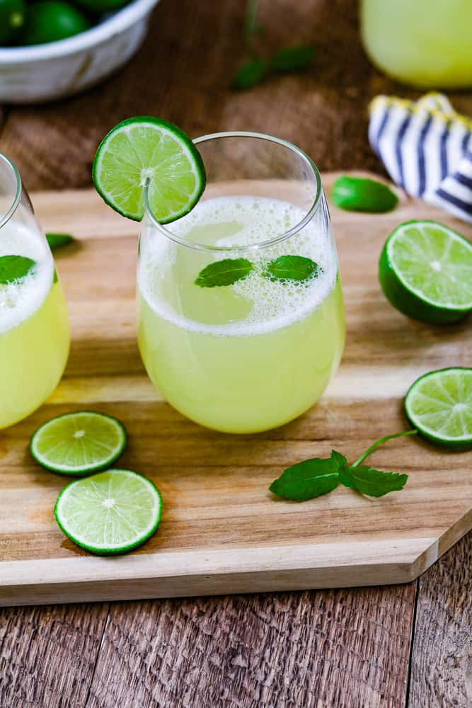 two glasses of limeade on top of a cutting board with lime and mint on the side.