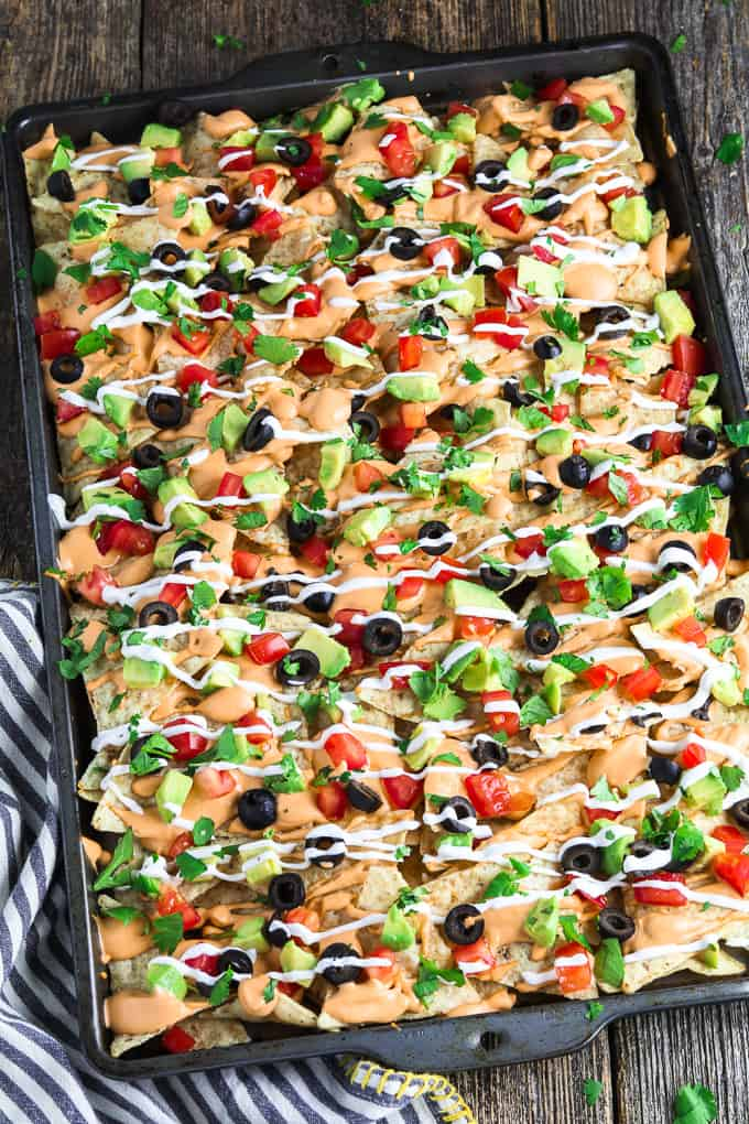Full overhead view of vegan nachos in a baking pan and loaded with all toppings. Striped napkin on the side.