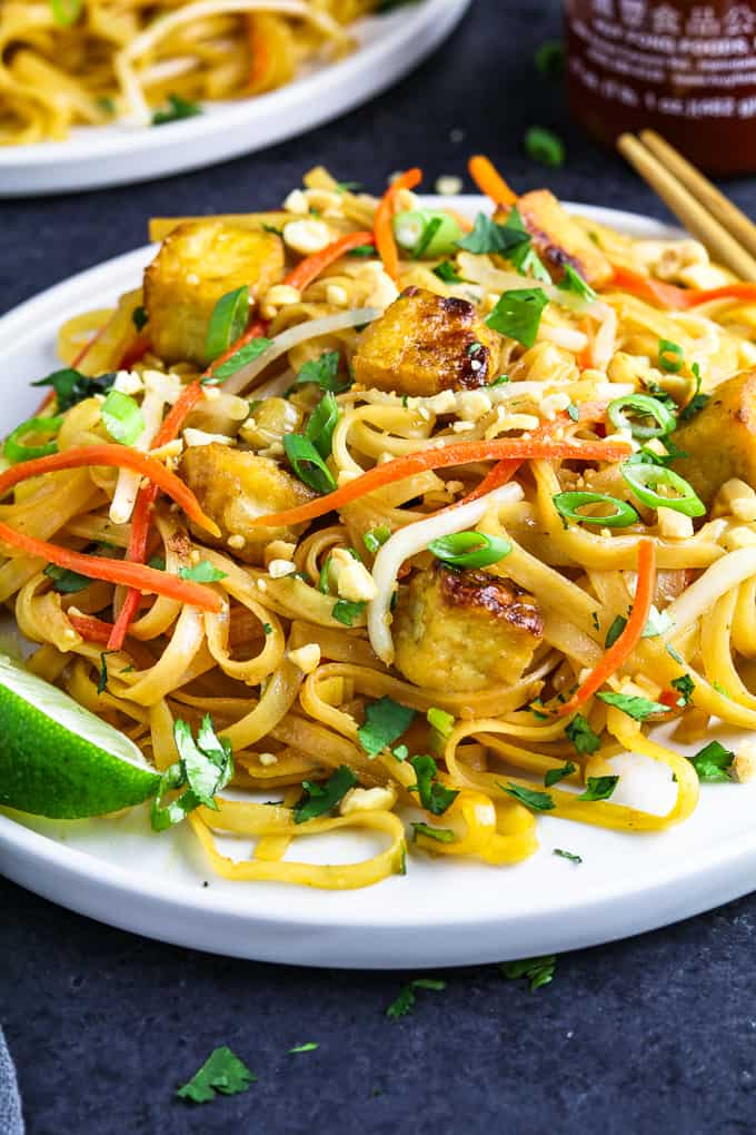 close up of freshly cooked vegan pad thai on a white plate. Lime wedge and chopsticks on the side.