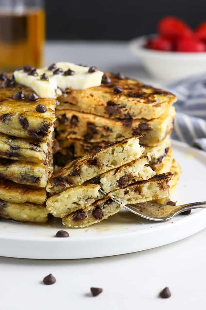 stack of vegan chocolate chip pancakes on a white plate with 3 pieces on a fork.