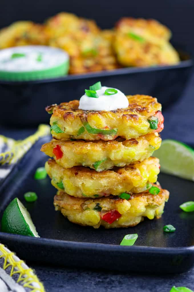 stack of four vegan corn fritters on a black plate. Topped with vegan sour cream and green onions.