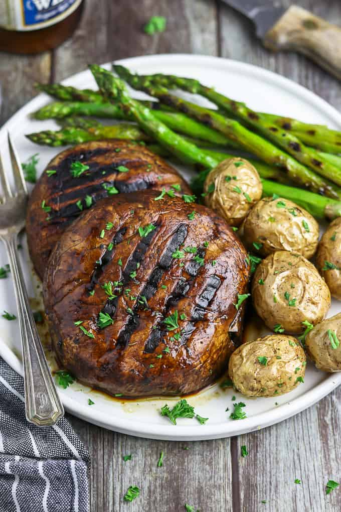 Two portobello mushroom steaks on a white plate with asparagus and potatoes on the side.