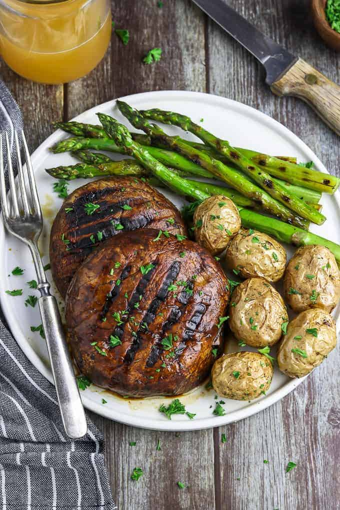 Overhead view of portobello mushroom steaks with potatoes and asparagus on the side.