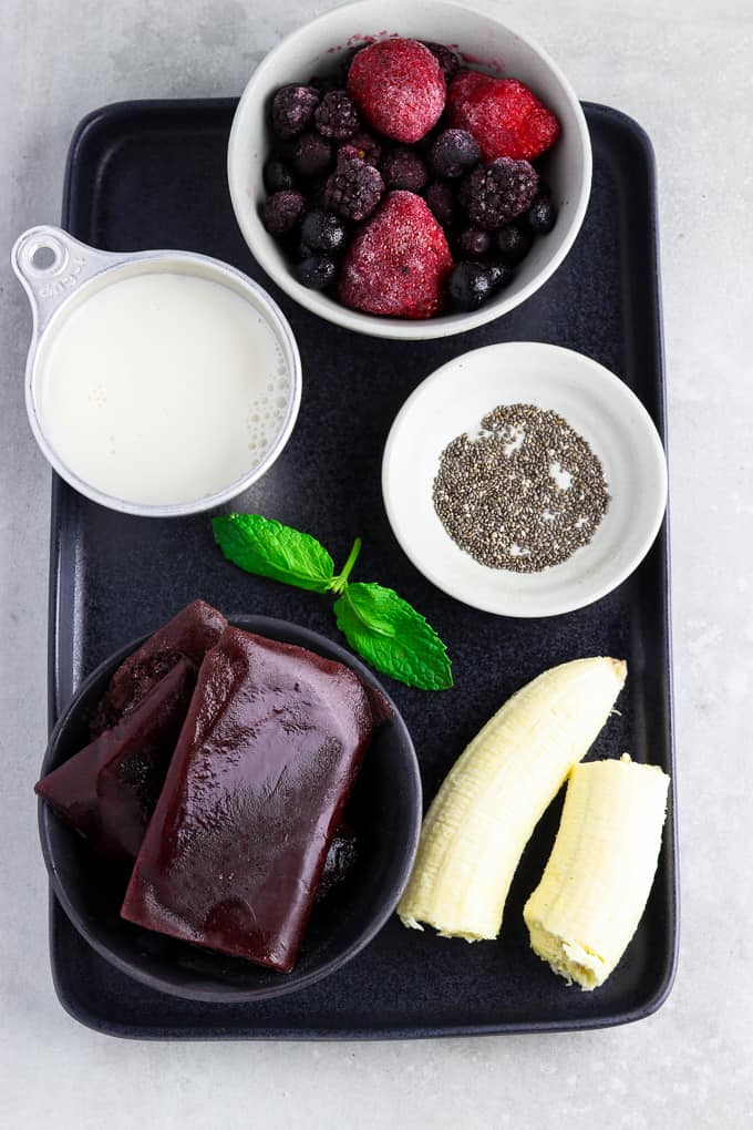 Ingredients on a black tray for acai bowl recipe.