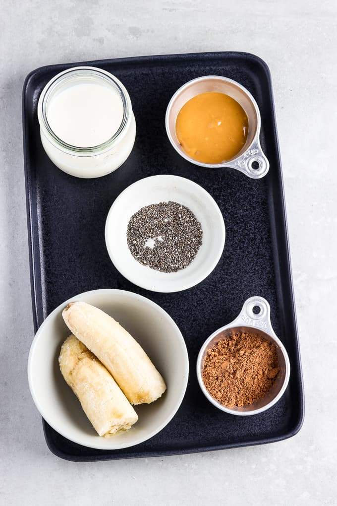 Ingredients for chunky monkey smoothie on a black serving tray.