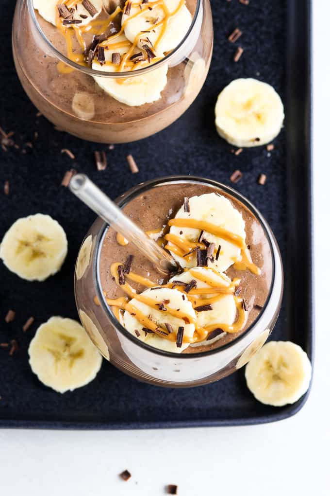 Overhead view of two smoothies on a black tray with banana slices and chocolate shavings on the side.
