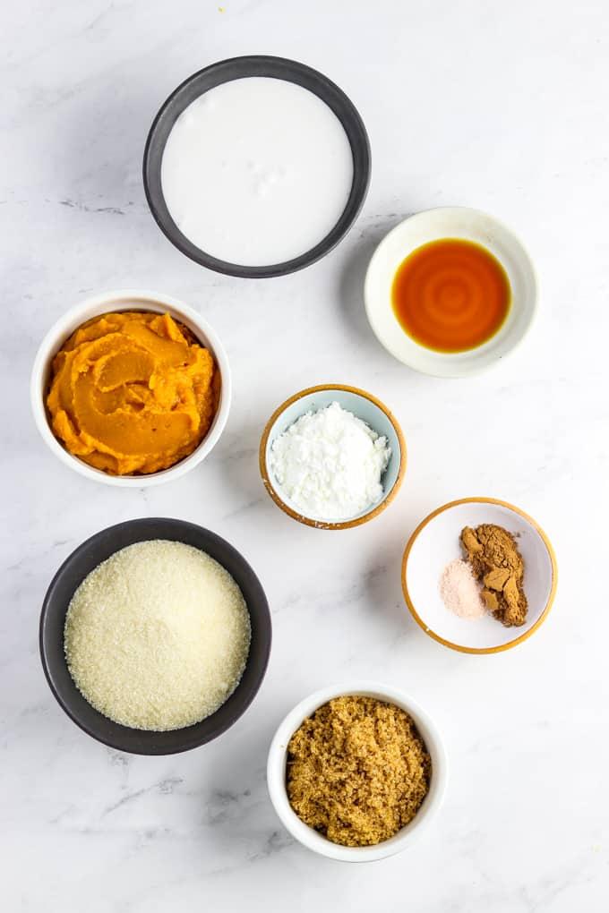 Ingredients for vegan pumpkin pie on a marble table top.