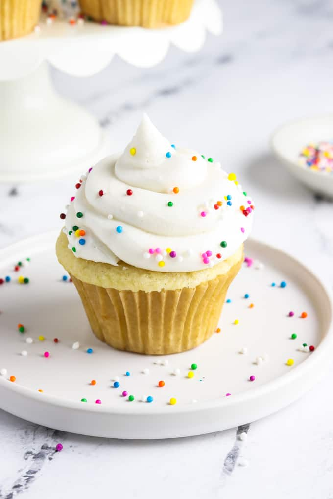 Overhead view of a vegan vanilla cupcake topped with sprinkles.