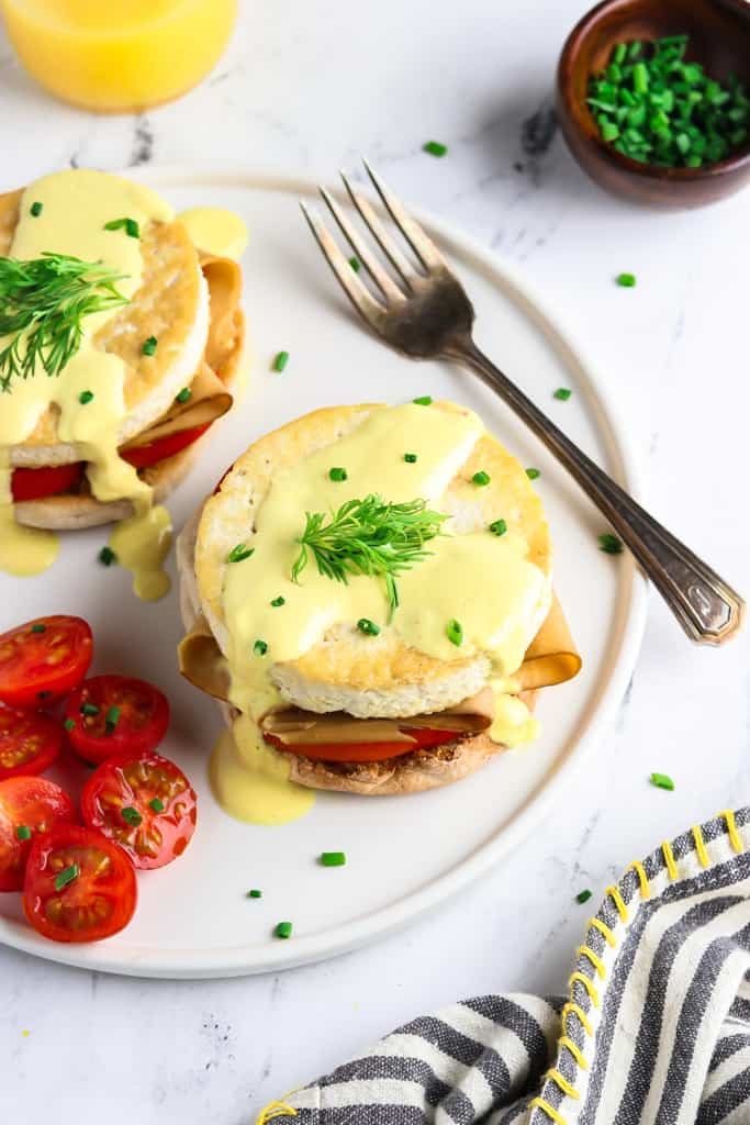 Overhead view of vegan eggs benedict on a white plate with orange juice, chives and napkin on the side.