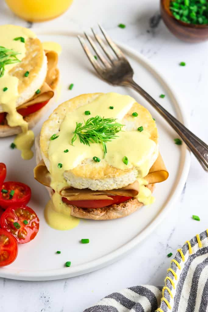 Vegan eggs benedict on a white plate with tomatoes and fork on the side.