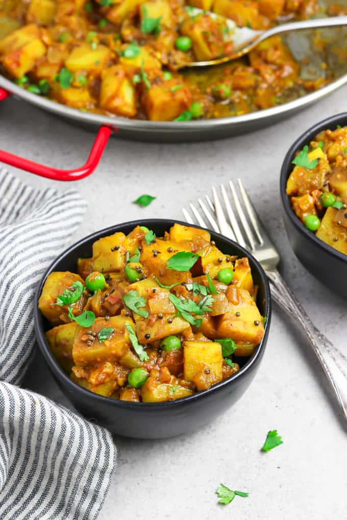 Two bowls filled with bombay potatoes with forks in the middle.