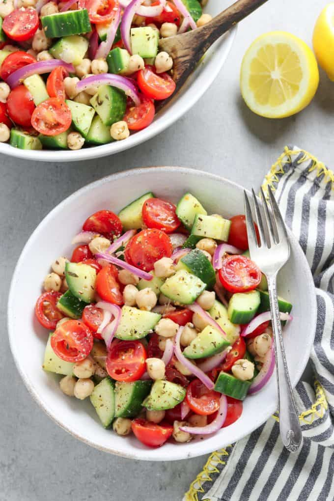 A white bowl filled with tomato and cucumber salad with a fork on the side. Serving bowl filled with salad in the background.