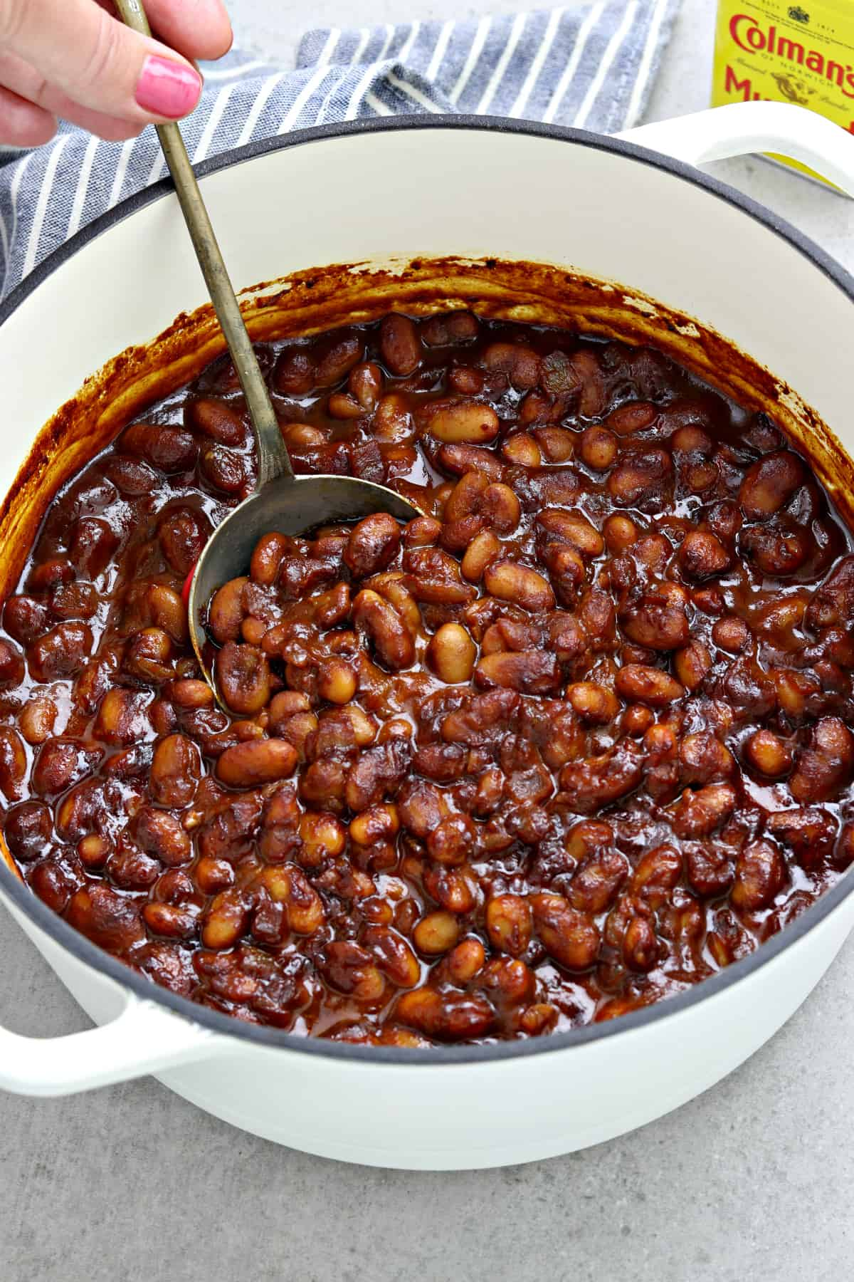 overhead view of baked beans in a white pot. Hand holding spoon and stirring beans.
