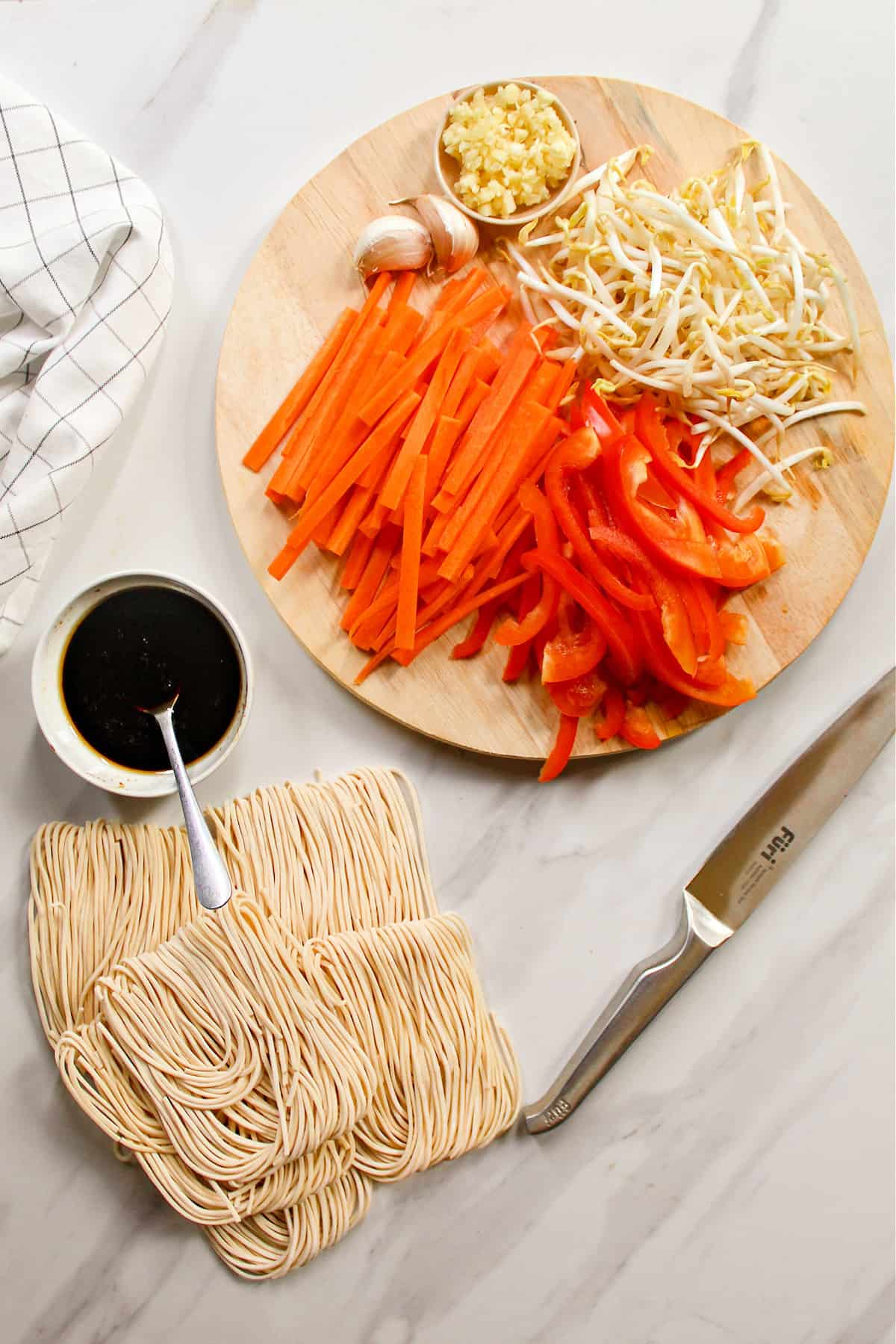 Ingredients top make the lo mein recipe on a white marble table top.