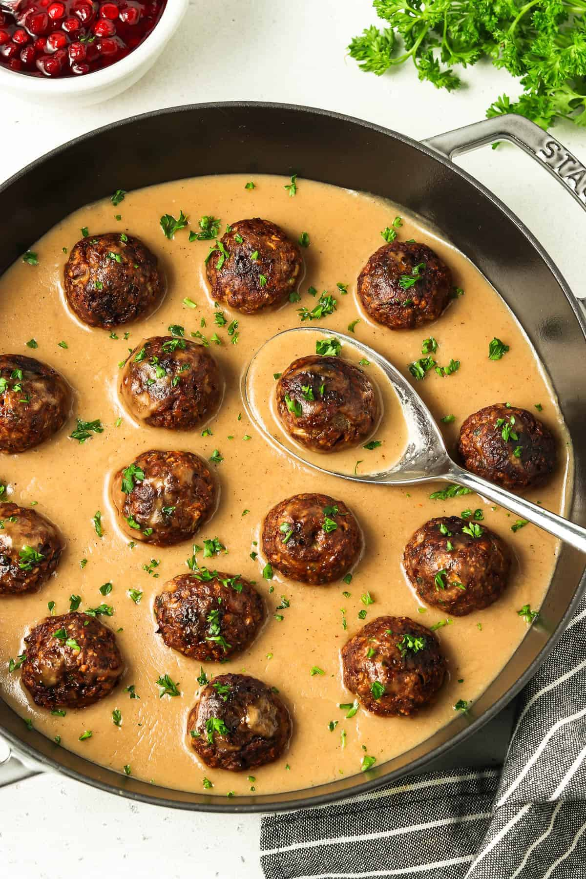 overhead view of fully cooked vegan Swedish meatballs in a gray pan. Serving spoon inside.