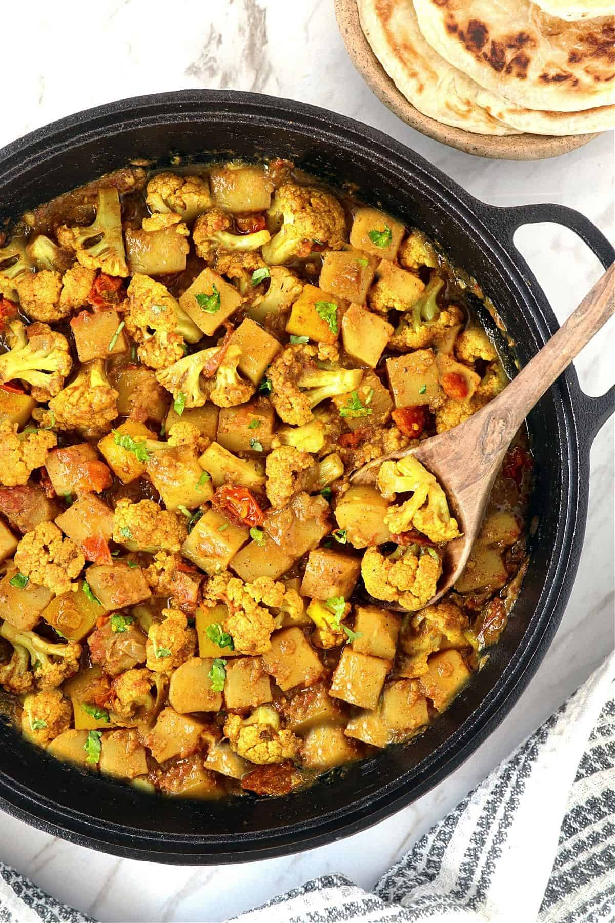 Close up view of fully cooked potatoes and cauliflower in a pan.