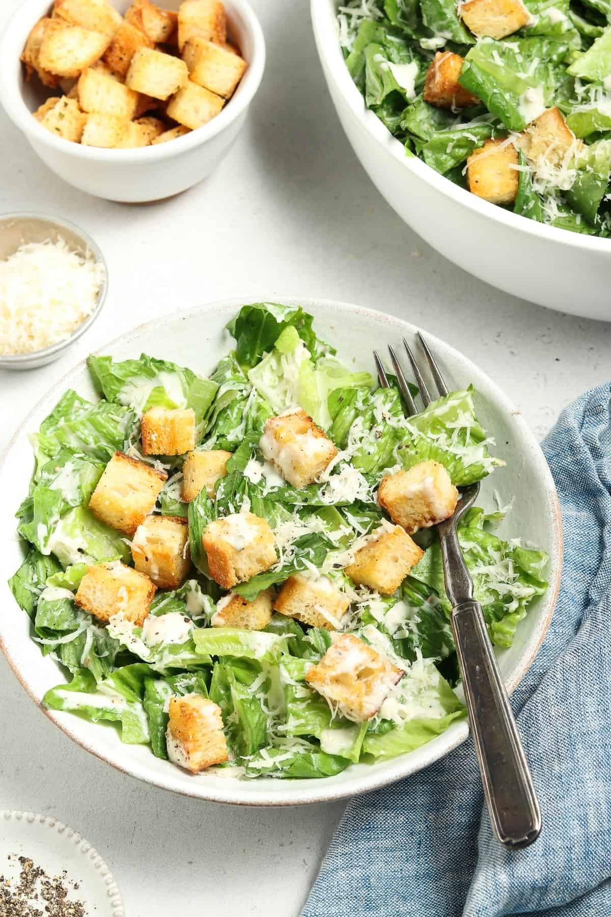 Front view of a bowl of vegan caesar salad with a fork on the side. More salad in the background.