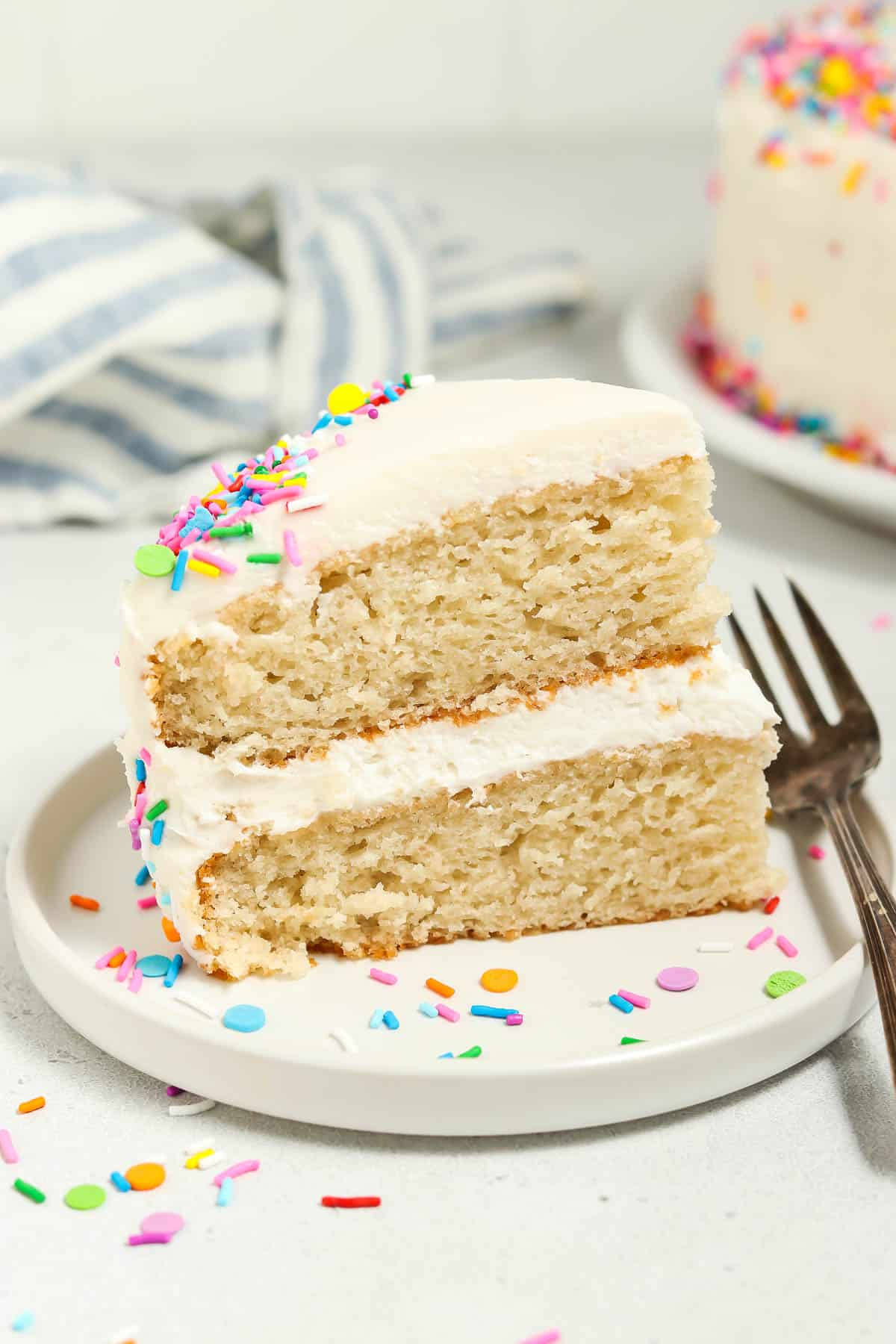 Side view of a slice of vegan vanilla cake on a white plate with sprinkles and fork on the side.