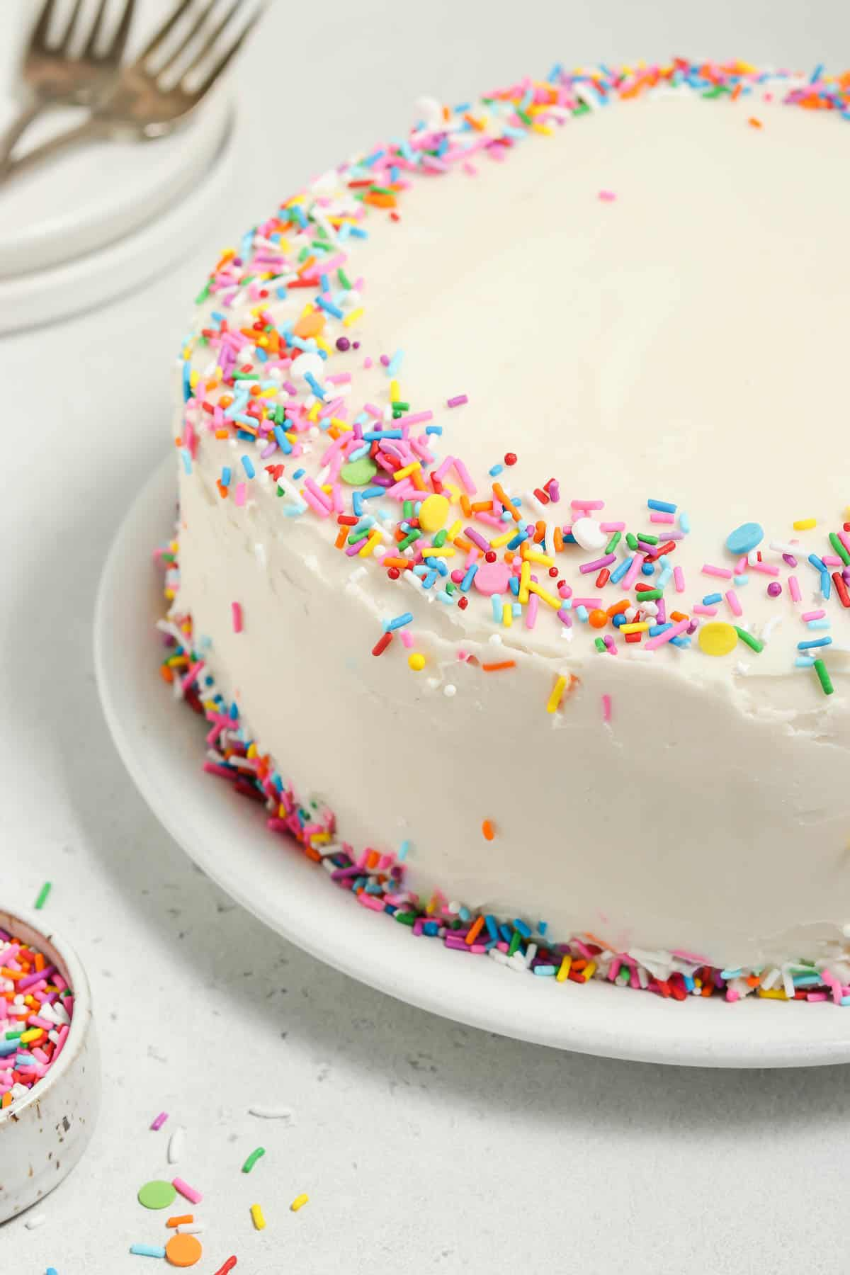 Front view of a whole vegan vanilla cake on a cake plate. Sprinkles, plates and forks on the side.
