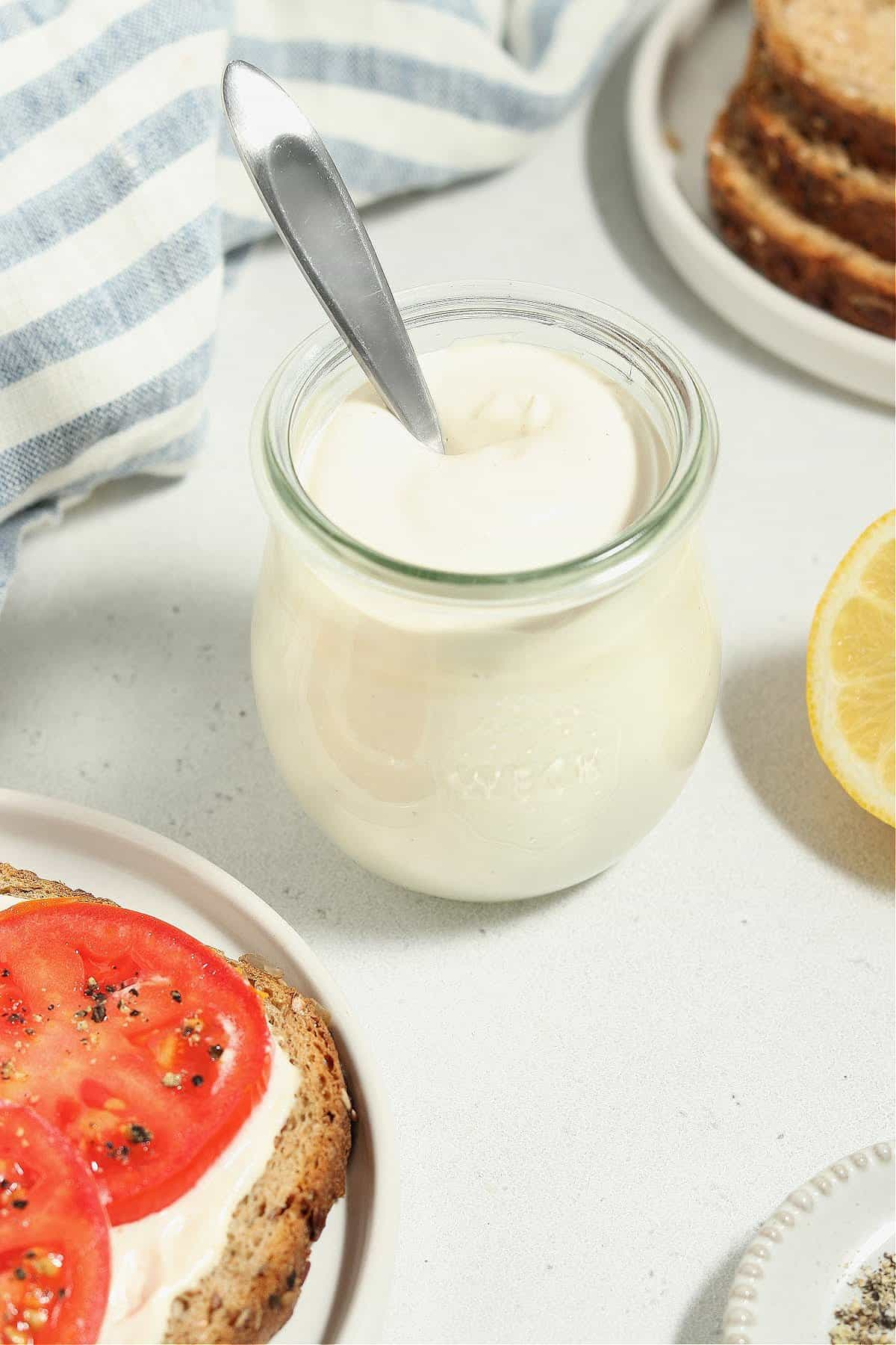 Close up view of vegan mayo in a jar with a spoon sticking out.