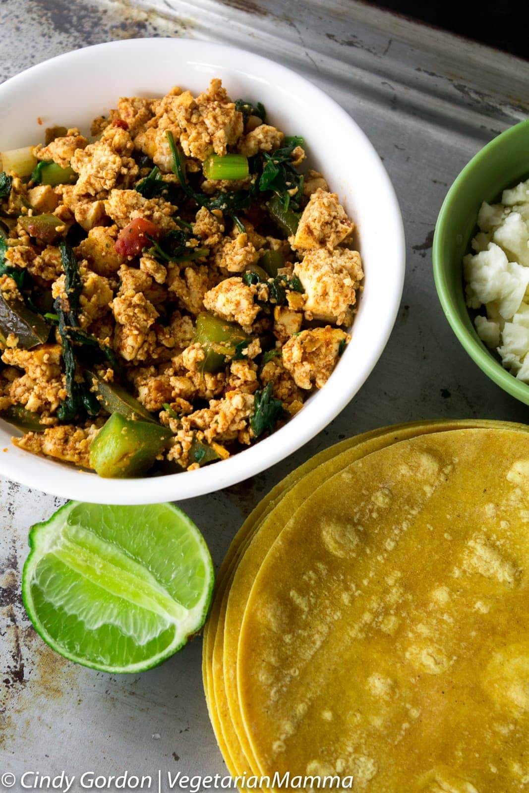 A white bowl with brown tofu crumbles scrambled with vegetables and herbs