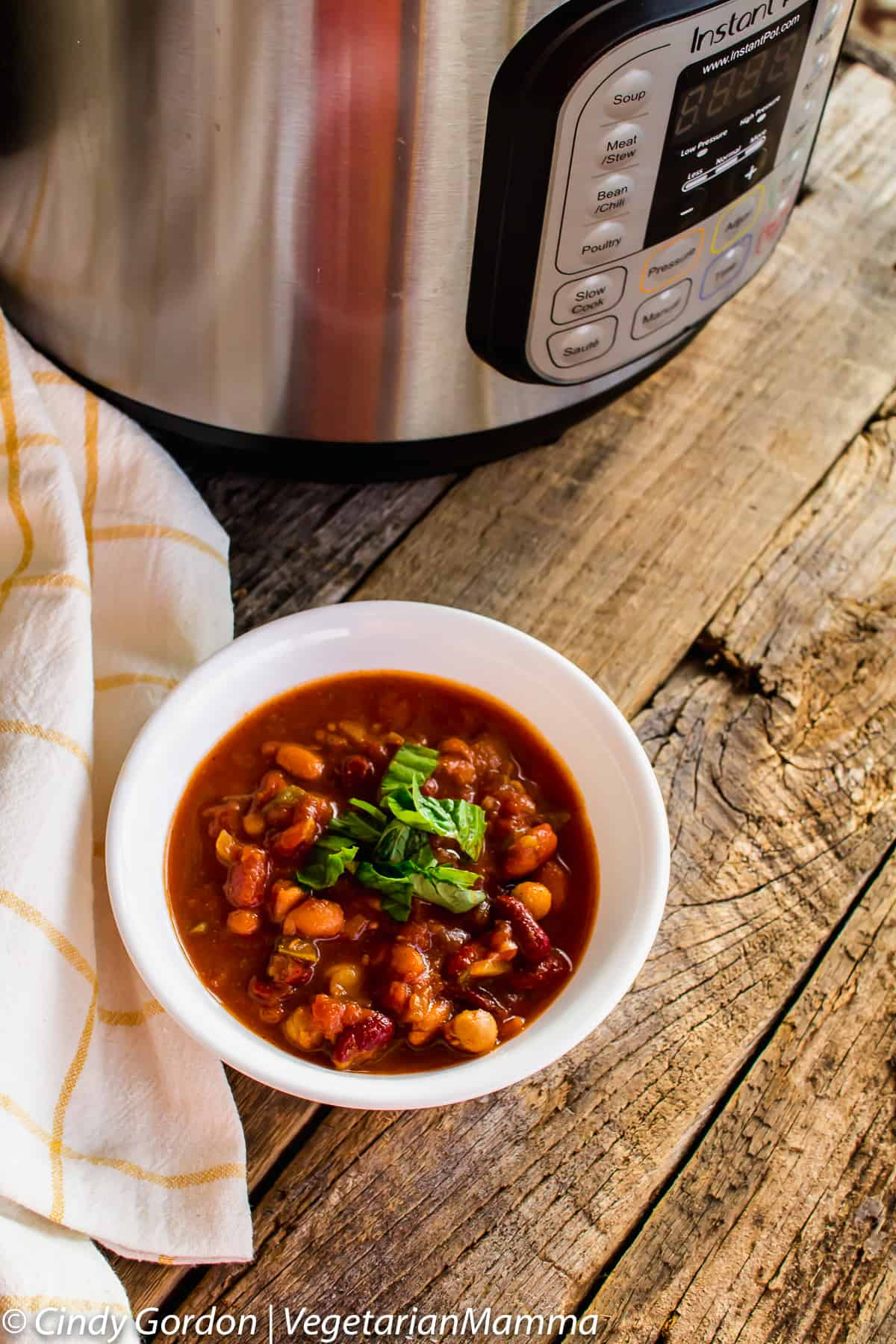 bowl of Instant Pot Four Bean Chili next to an instant pot