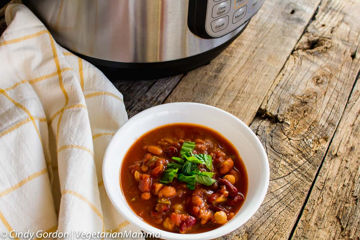 bowl of Instant Pot Four Bean Chili topped with fresh herbs