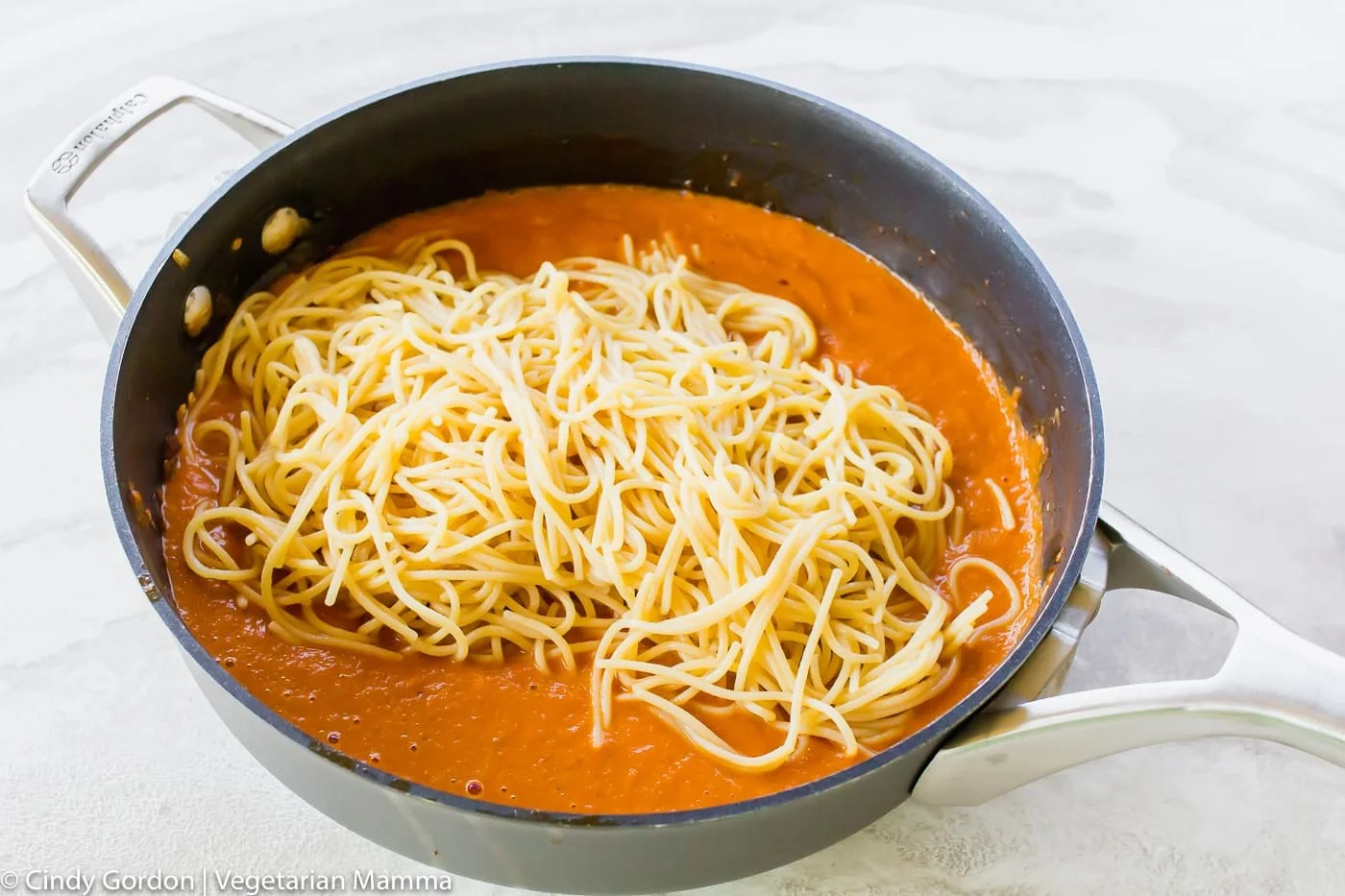 picture of sauce in skillet with cooked pasta on top, unmixed.