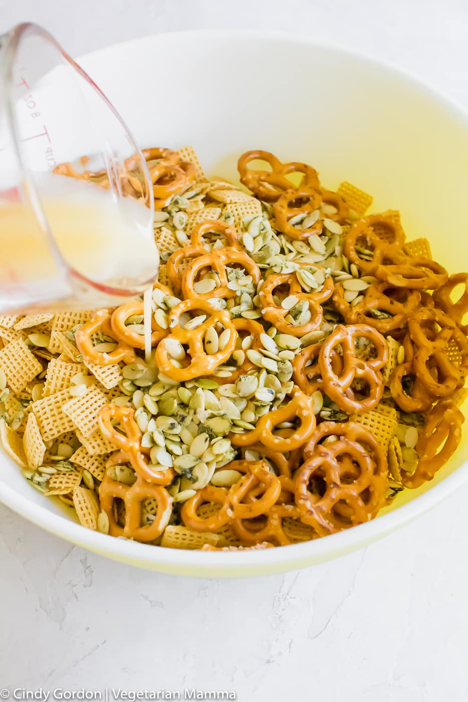 melted butter being poured into air fryer chex mix ingredients
