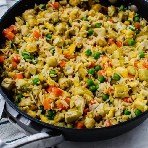 a black skillet filled with tofu fried rice and vegetables