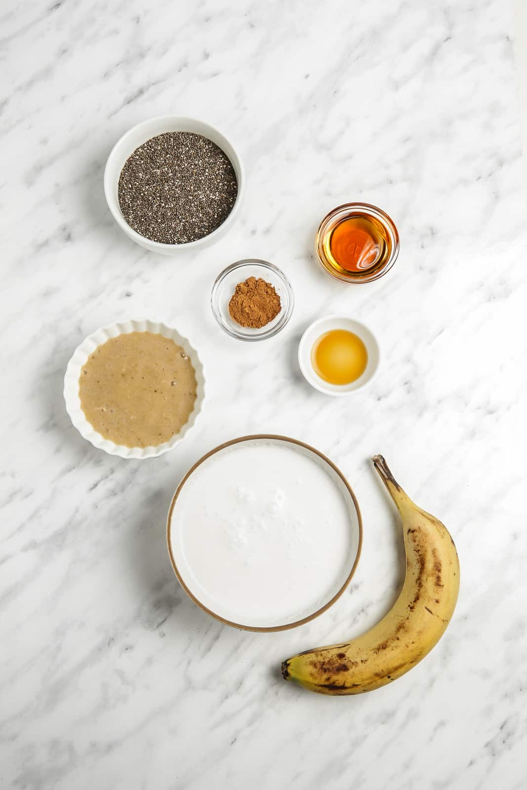 Bowls of chia seeds, maple syrup, coconut milk, vanilla syrup, cinnamon,  and mashed banana with a fresh banana