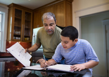 Grandfather helping boy with homework