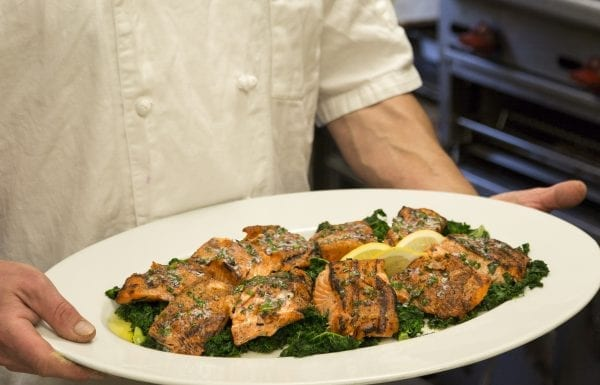 Maple glazed salmon on a bed of spinach.