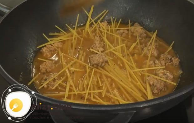 Біз спагеттиді жартысынан сындырып, табаға саламыз.