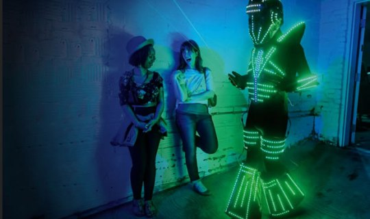Media Arts   NEA Two women in a darkened room watch a man dressed in a kind of space suit