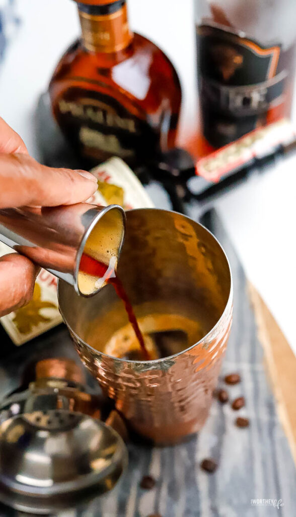 pouring dark rum into a cocktail shaker