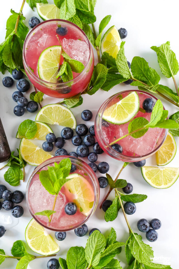 Blueberry Mojito in three glasses with fruit