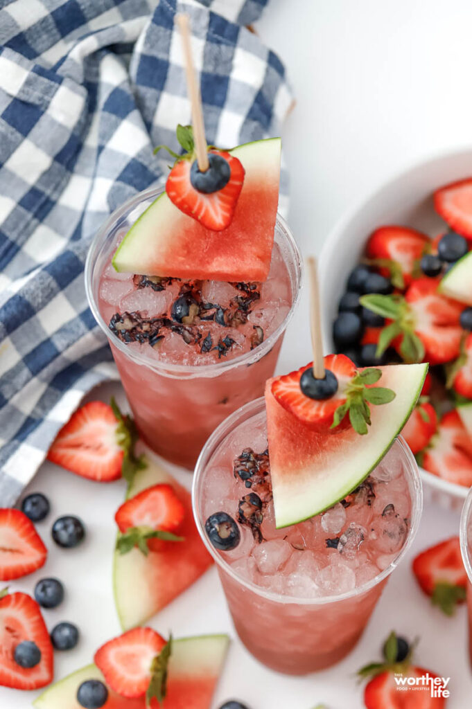 party cups filled with a watermelon berry drink with a fresh fruit garnish