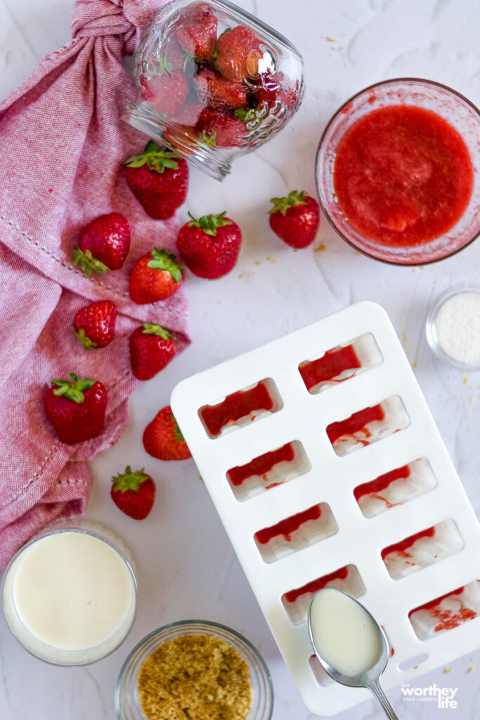 the making of frozen popsicles with strawberries