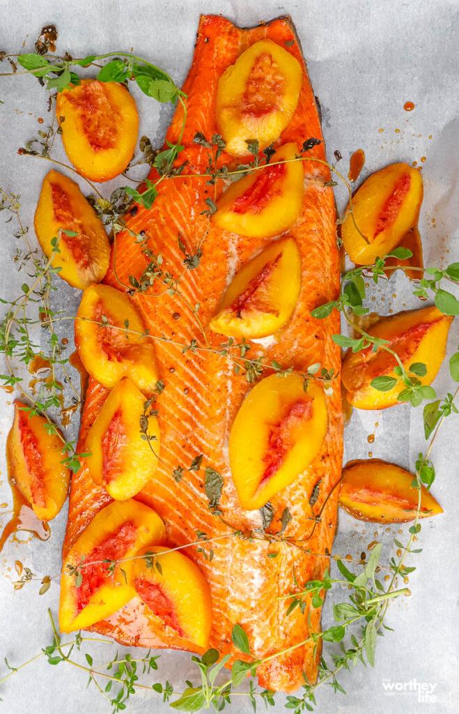 fresh salmon with peaches on baking sheet