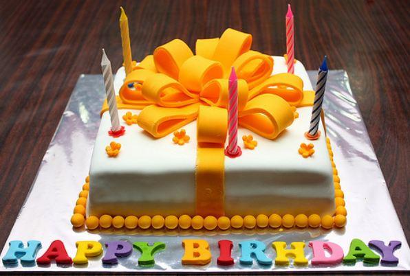 White Birthday Cake With Large Orange Ribbon And Happy